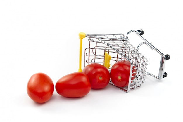 Um tomate no carrinho de compras isolado no fundo branco. tomates vermelhos saborosos maduros no carrinho de compras. conceito de negociação de tomate. conceito de compras on-line. carrinho e tomate sobre um fundo branco.