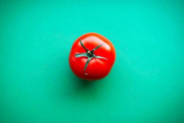 Um tomate vermelho sobre uma superfície verde.