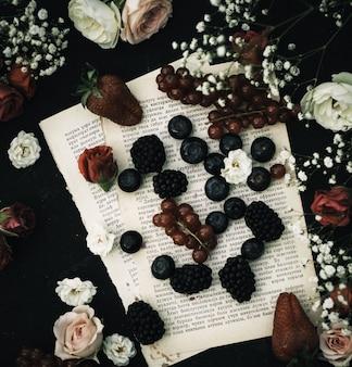 Um top close-up frutas frescas, como mirtilos e amoras, juntamente com outras pessoas no chão de papel e escuro