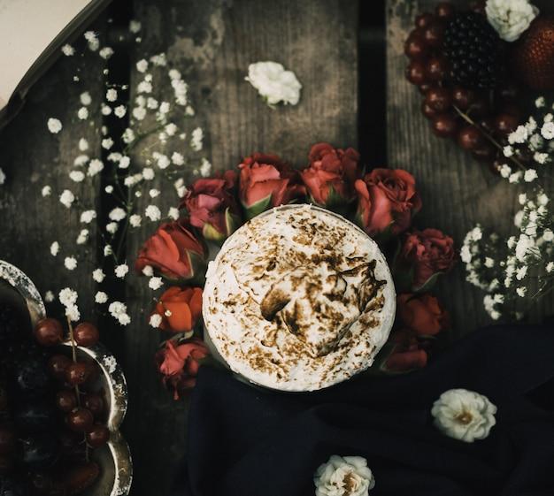Um top close-up vista café quente gostoso nas rosas vermelhas e superfície rústica de madeira marrom