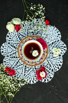Um top close-up vista chá quente dentro de copo sobre o tecido branco sobre a mesa escura