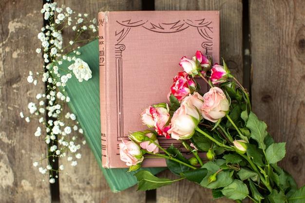 Um top close-up vista livros e rosas no chão de madeira marrom