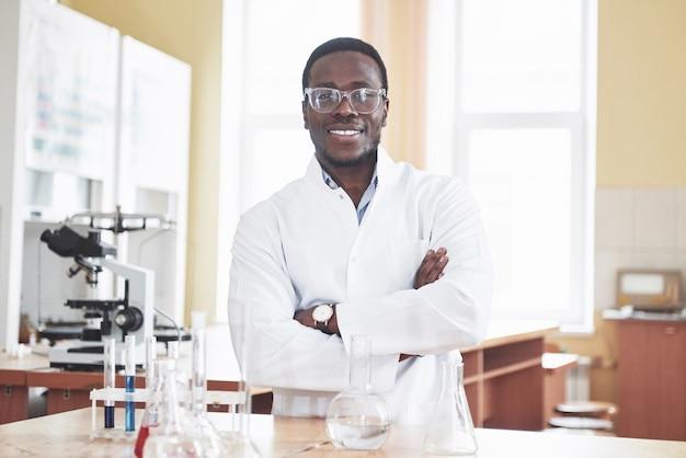 Um trabalhador afro-americano trabalha em um laboratório conduzindo experimentos.