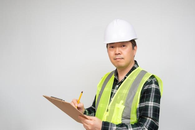 Um trabalhador asiático de meia-idade, verificando algo com uma lista de verificação na mão.