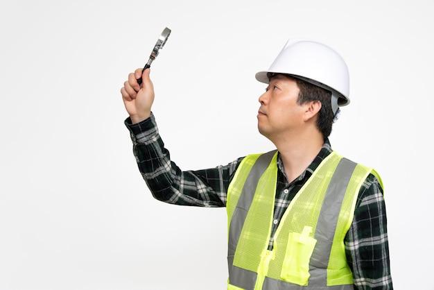 Um trabalhador asiático de meia-idade, verificando algo com uma lupa na mão.