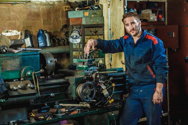 Um trabalhador cansado em um traje de proteção azul está de pé ao lado de uma máquina de tornear
