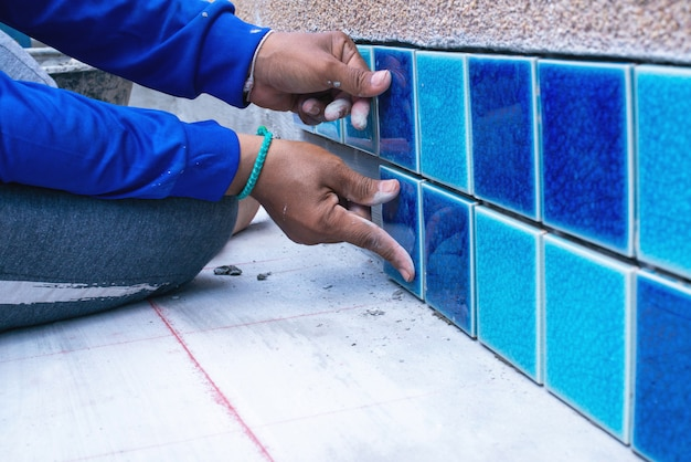 Um trabalhador colocando telhas em casa reparar, instalação de telhas na cola