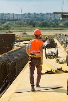 Um trabalhador com capacete de segurança caminha pela área de construção