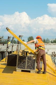 Um trabalhador com capacete de segurança pega uma viga de construção amarela