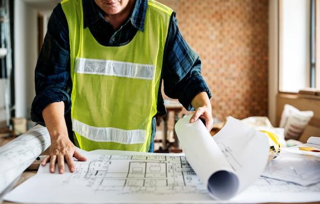 Um, trabalhador, com, um, capacete duro, lokking, para, um, blueprint