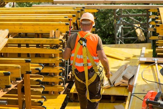 Um trabalhador com um capacete e cintos de segurança no fundo de vigas de construção amarelas