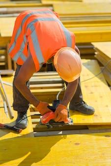 Um trabalhador com um capacete protetor serra uma prancha de madeira em um canteiro de obras