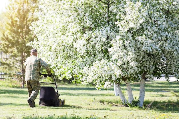 Um trabalhador corta o gramado no jardim.