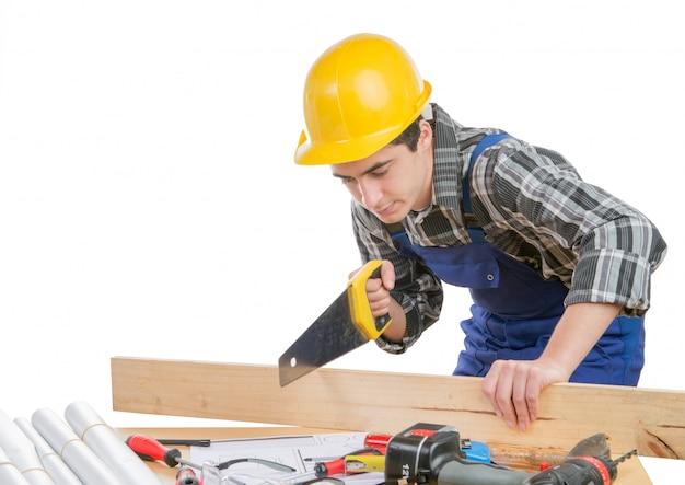Um trabalhador corta uma prancha de madeira com uma serra manual