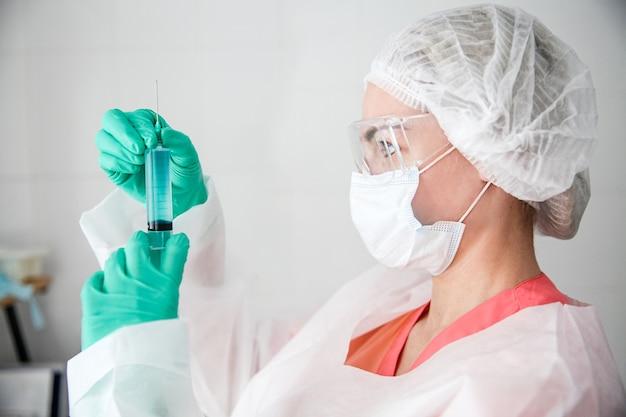 Um trabalhador da área médica com luvas verdes, um boné branco, um traje de proteção e uma máscara no rosto segurando uma seringa com uma vacina
