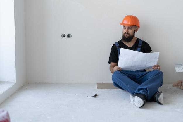 Um trabalhador da construção civil brutal com uma barba usa um uniforme de trabalho e uma máscara laranja. sentado no chão. examine desenhos antigos no papel. pensa e desvia o olhar. lugar para texto. copie o espaço.
