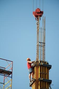 Um trabalhador da construção civil controla o movimento do guindaste ao montar blocos de construção contra um céu azul