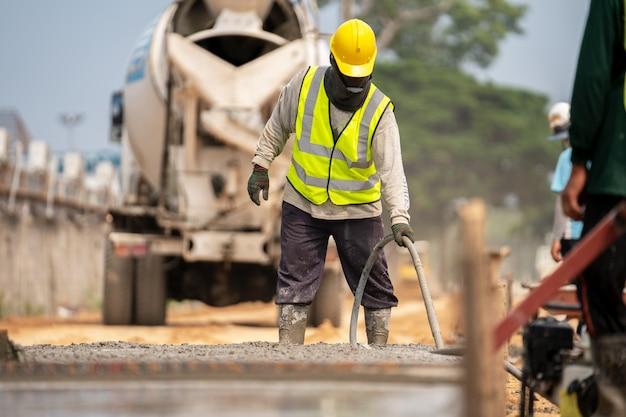 Um trabalhador da construção civil derramando um concreto molhado no local da construção de estradas