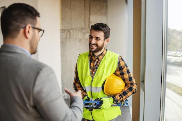 Um trabalhador da construção civil em pé com o arquiteto e discutindo sobre a construção