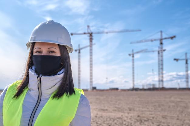 Um trabalhador da construção civil feminino em uma máscara preta