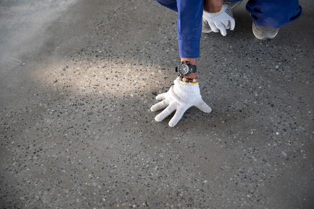 Um trabalhador da construção civil verificar piso epóxi de qualidade na fábrica de armazém japão construção si