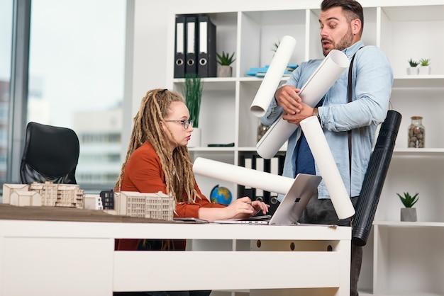 Um trabalhador de escritório desajeitado espalhando desenhos sobre a mesa de sua gerente feminina séria e descontente.