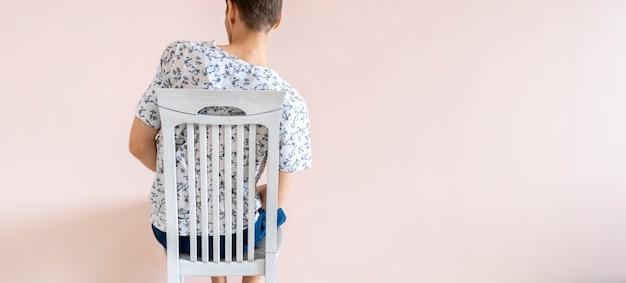 Um trabalhador de escritório do sexo masculino sentado casual com má postura, problemas de dor nas costas, conceito simples e isolado