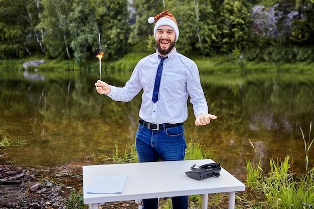 Um trabalhador de escritório está de pé perto da mesa e segurando uma vela acesa de bengala na mão.