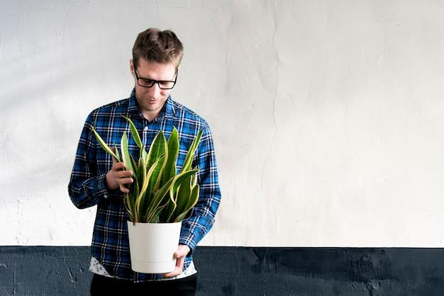 Um trabalhador de jardim segurando um vaso com flores em uma estufa, viveiro de plantas