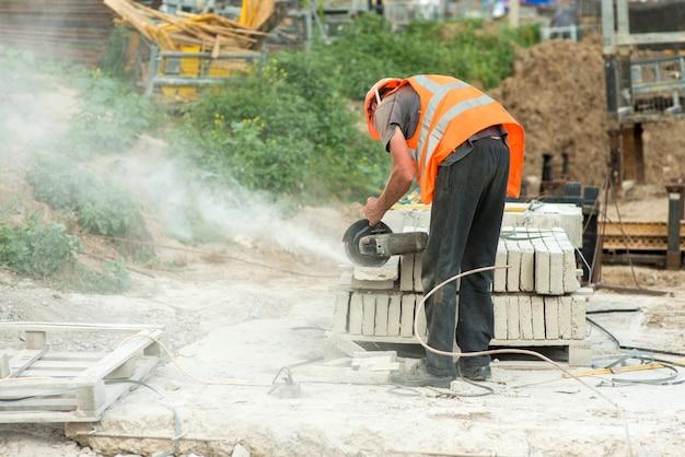 Um trabalhador de macacão corta um pedaço de meio-fio de concreto usando um moedor elétrico