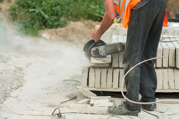 Um trabalhador de macacão corta um pedaço de meio-fio de concreto usando um triturador elétrico, close-up
