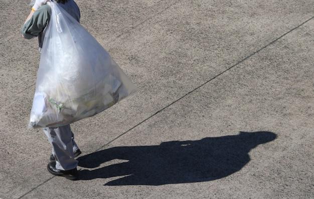 Um trabalhador de manutenção de lixo carregando um saco de lixo plástico em dia ensolarado.