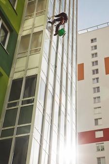 Um trabalhador de montanhismo industrial se debruça sobre um prédio residencial enquanto lava os vidros exteriores da fachada. trabalhador de acesso por corda pendurado na parede da casa. conceito de obras urbanas. copie o espaço