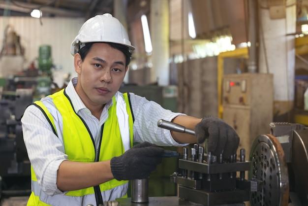 Um trabalhador de óculos em pé perto de equipamento industrial e verifica a produção. homem operando máquina na fábrica