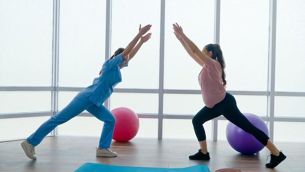 Um trabalhador de saúde em um centro médico ajuda uma mulher grávida a fazer exercícios
