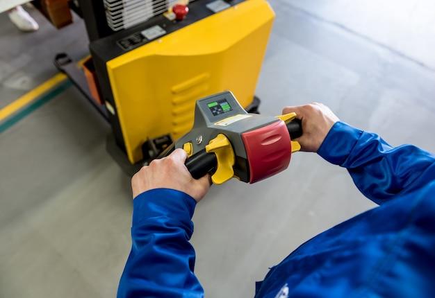 Um trabalhador em um depósito usa um empilhador manual de paletes para transportar paletes.