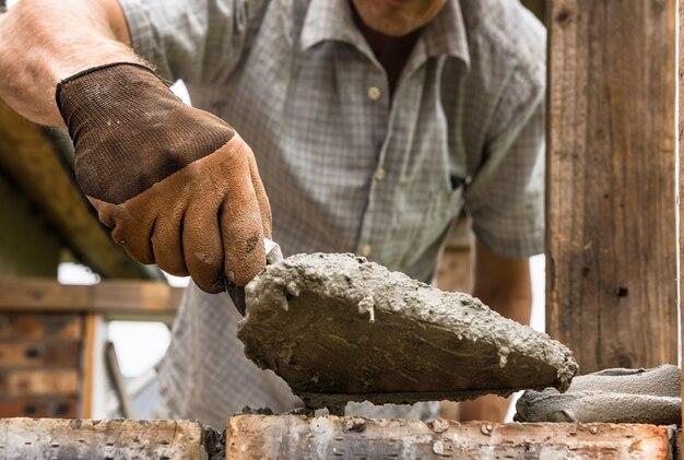 Um trabalhador está aplicando uma argamassa com uma espátula no tijolo