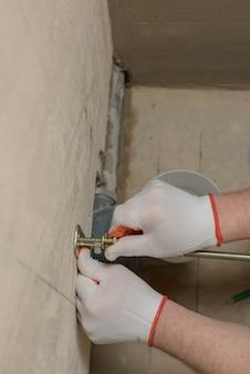 Um trabalhador está consertando uma parede de parafusos
