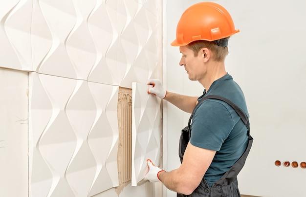 Um trabalhador está fixando a placa de gesso na parede