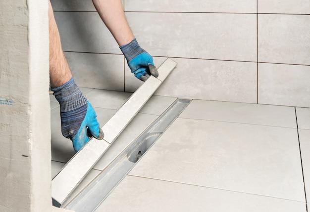 Um trabalhador está instalando uma tampa de ralo decorada com ladrilhos de cerâmica no banheiro