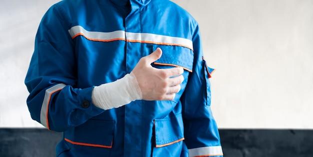 Um trabalhador industrial do sexo masculino em uniforme com curativo ferimento em primeiros socorros