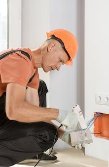 Um trabalhador instala e conecta a fonte de alimentação da luz de fundo led.