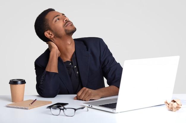 Um trabalhador masculino de pele escura sonhador tem dor no pescoço, mantém o olhar para cima, trabalha por muito tempo na área de trabalho, prepara nova publicação sobre o tema de negócios, bebe bebida quente, isolada na parede branca