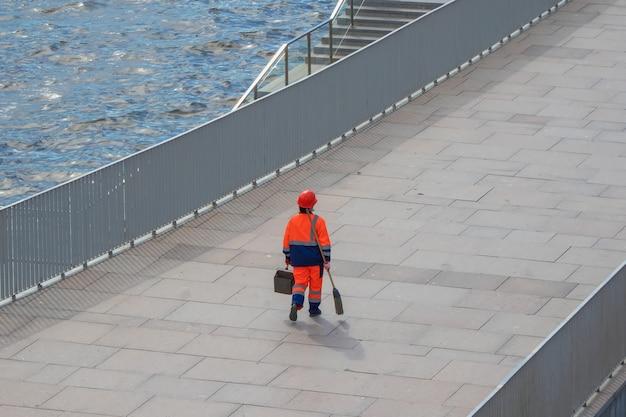 Um trabalhador municipal em uma rua da cidade, um zelador com uma vassoura e uma pá de lixo nas mãos.