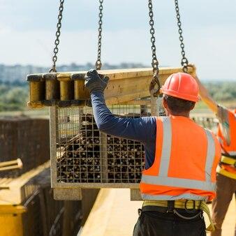 Um trabalhador pega uma carga de um guindaste de construção