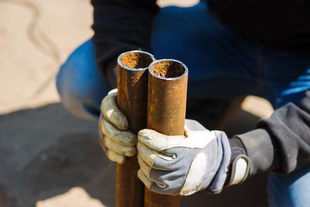 Um trabalhador segura nas mãos dois pedaços de um tubo de metal cortado