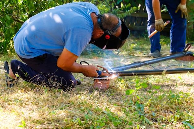 Um trabalhador usando uma máscara protetora solda tubos de metal com soldagem a arco elétrico