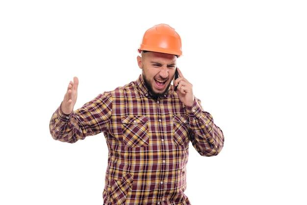 Um trabalhador zangado e nervoso com um capacete laranja está falando alto ao telefone, gritando ao telefone. fundo branco isolado
