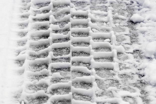 Um traço claro de um pneu de carro na neve