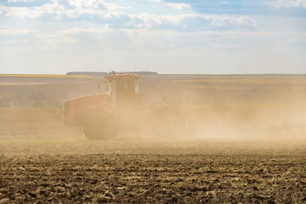 Um trator agrícola vermelho em uma nuvem de poeira cultiva o solo no campo